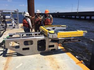 A powerful concrete saw is deployed to trim piles that will provide the foundation for the new Pensacola Bay Bridge.